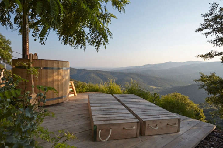A Swedish style tub and two sun beds (made from recycled palettes) take in the views of distant hills in a Tuscan retreat. Photograph by Julia Speiss.