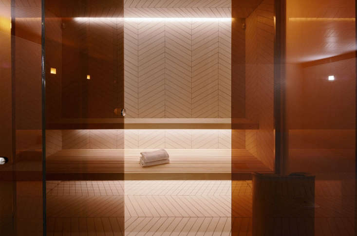 A sauna and shower is obscured behind amber-tinted glass in the underground, indoor pool area.