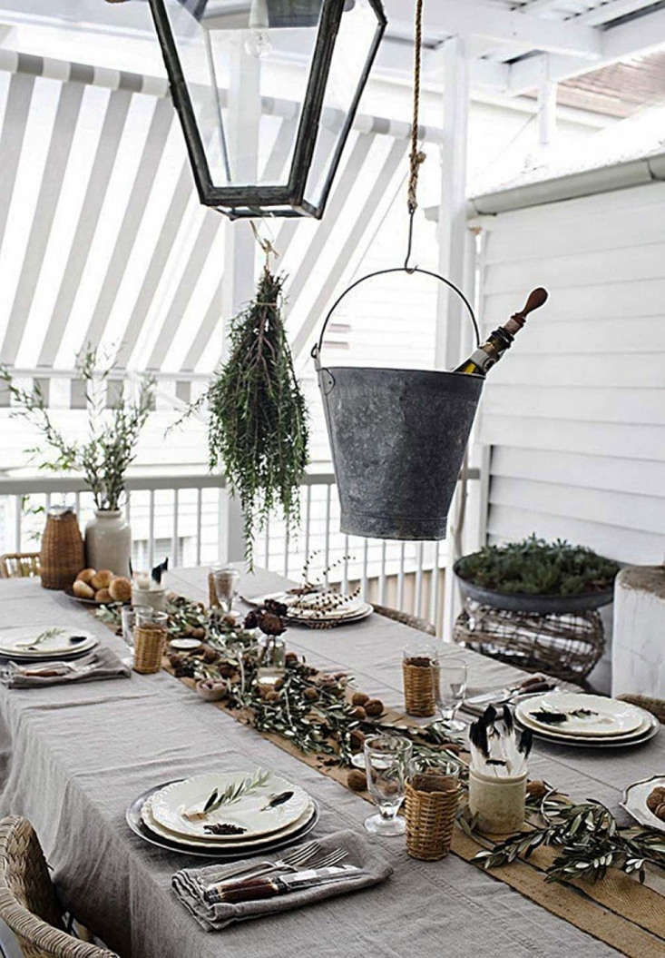 Australian designer Kara Rosenlund hung a bunch of rosemary from the pendant light over her dining table and dressed the table with clippings of olive. For more, seeHouse Call: In the Kitchen and Beyond with Kara Rosenlund.