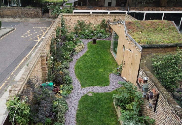 In a city garden in London, brick walls are softened by climbing vines and roses, as well as by espaliered apple trees.