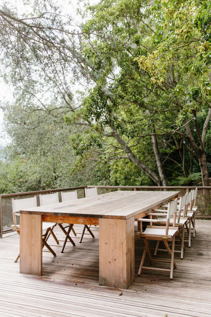 The house has outdoor living spaces on two levels, including a deck with an expansive wood dining table.