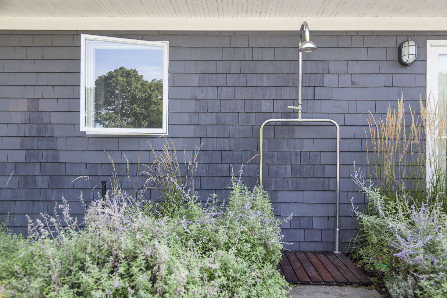 An alluring outdoor shower, partially hidden by tall grasses, is best utilized while wearing a bathing suit.