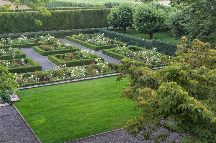 The walled rose garden, inspired by existing old roses, is laid out in a precise grid pattern. Dogwood trees (at R) soften the geometry of the sunken rose garden.