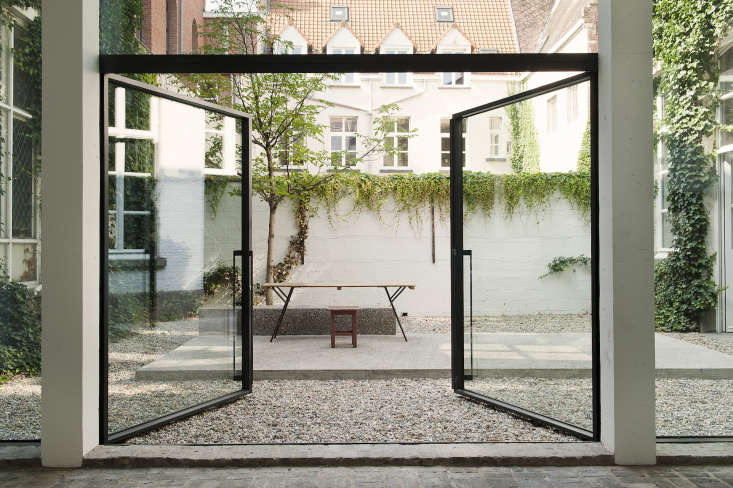 The courtyard in the Antwerp gallery-home of gallerist Veerle Wenes designed byLens°Ass Architects features nothing but gravel, sparse vines, a single tree, and elevated concrete floor. Photograph courtesy of Verne, fromSteal This Look: An Artful Gravel Garden in Antwerp.