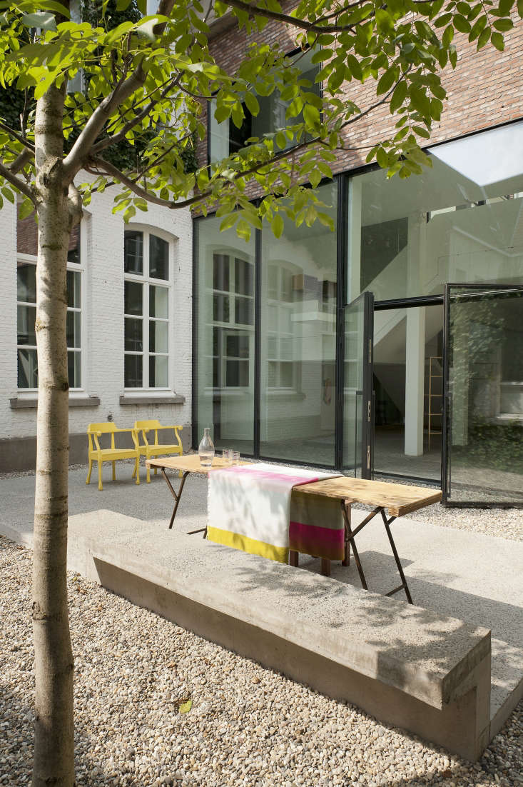 A wood table on iron folding legs and a pair of Muuto yellow chairs make up all the furniture in the garden. Photograph courtesy of Verne.