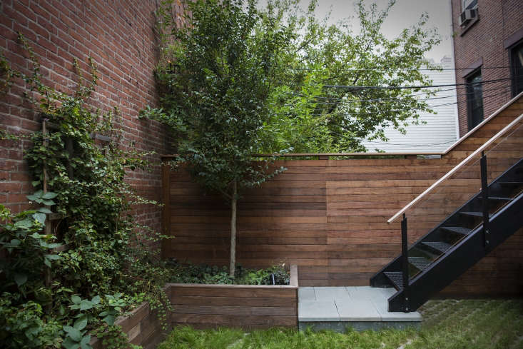 The planters and fence in the back garden were custom built. This area, meant for parking a car, has a driveway paved with permeable cement blocks in a diamond grid.