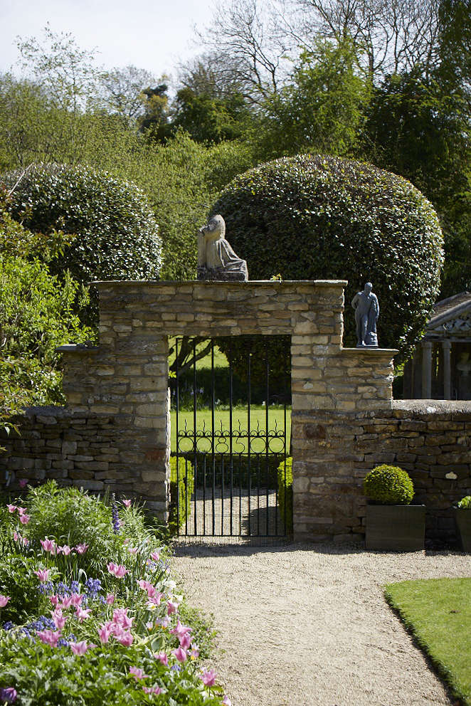 A French limestone statue of a kneeling figure tops the gate leading from the walled garden to the lower terrace, with the ironwork date '85', marking the start of Jessica and Simon's gardening story at Wortley House.