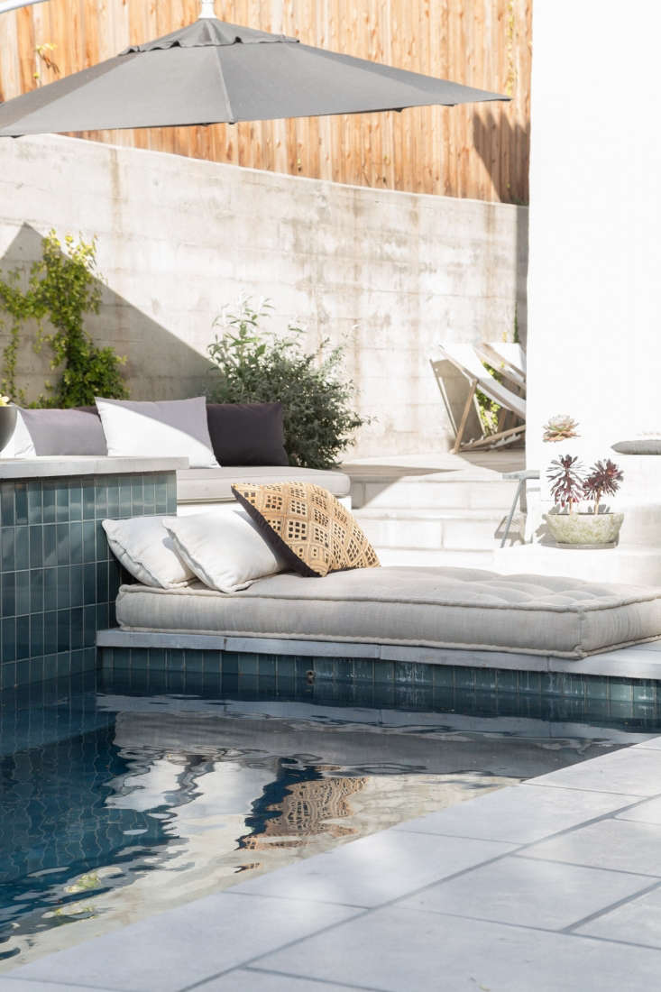 Another clever use of the hardscaping: A low cushion and pillows are positioned against the side of the pool to create a luxurious lounge spot, no furniture needed.