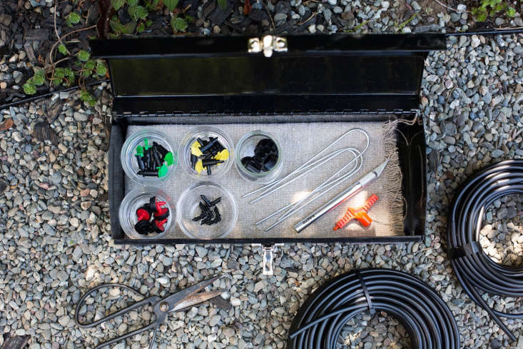 This drip irrigation kit&#8\2\17;s components include three different flow emitters, \1/4&#8\243; connectors, metal staples, an orange poker for creating holes for new emitters, end caps, a knife for cutting tubing, and tubing.