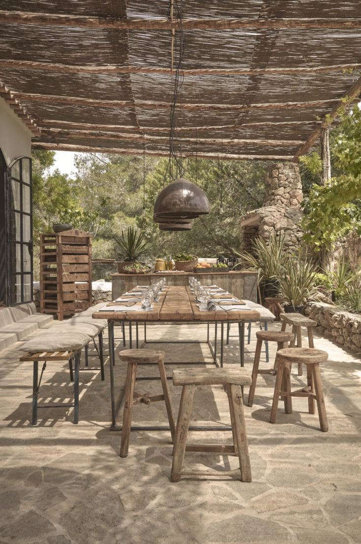 A woven cane pergola shades an outdoor dining patio. For more, see La Granja Ibiza: The Sexy New Farm Retreat. Photograph courtesy of Design Hotels.
