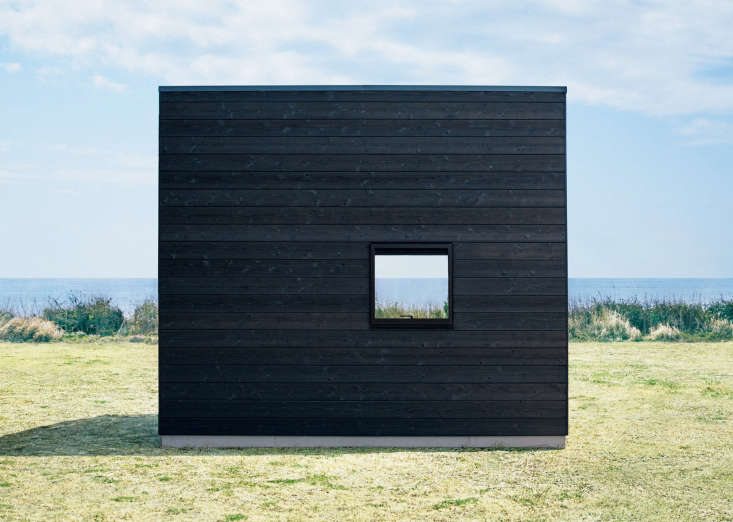From the back, the black Muji Hut has a simple profile. Thecharred siding is blackened bya traditional shou sugi ban technique.