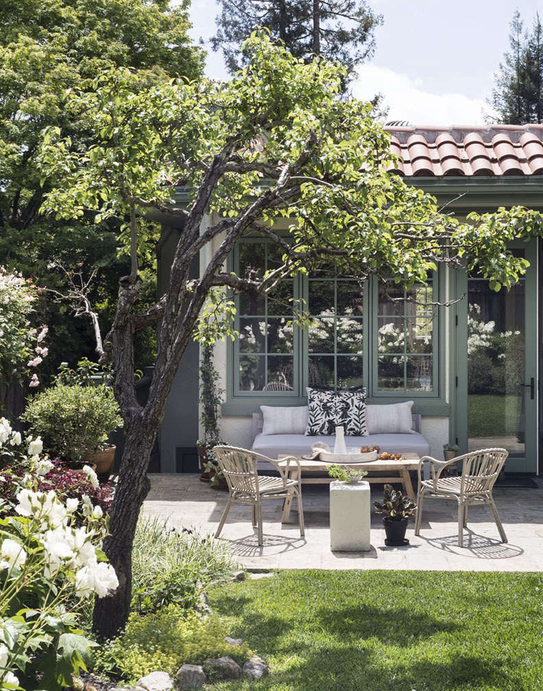 A bluestone patio serves as my outdoor living room, furnished with a pair of Ikea armchairs, a teak sofa, a flea market coffee table, and a ceramic stool I bought at a deep discount at a Serena & Lily outlet store (the stool has a chip on its base).