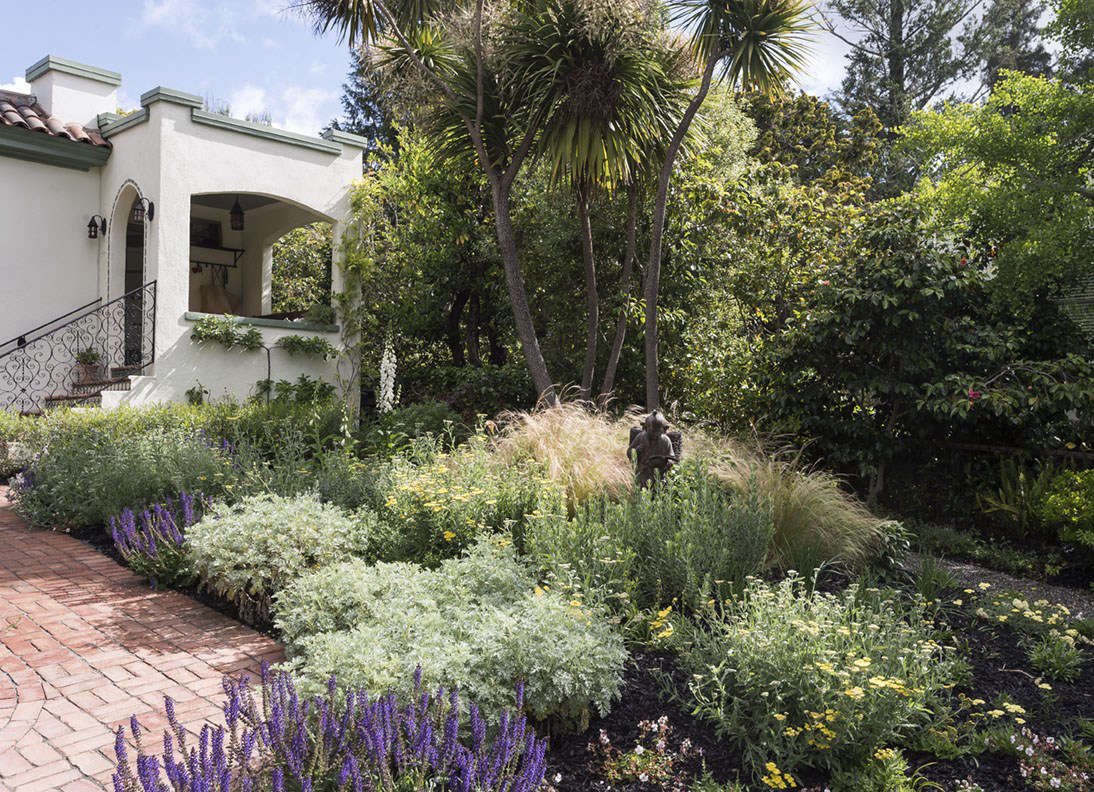 Rather than trying to change the grade of my sloping front garden, I planted perennials and grasses that would accentuate the lay of the land.