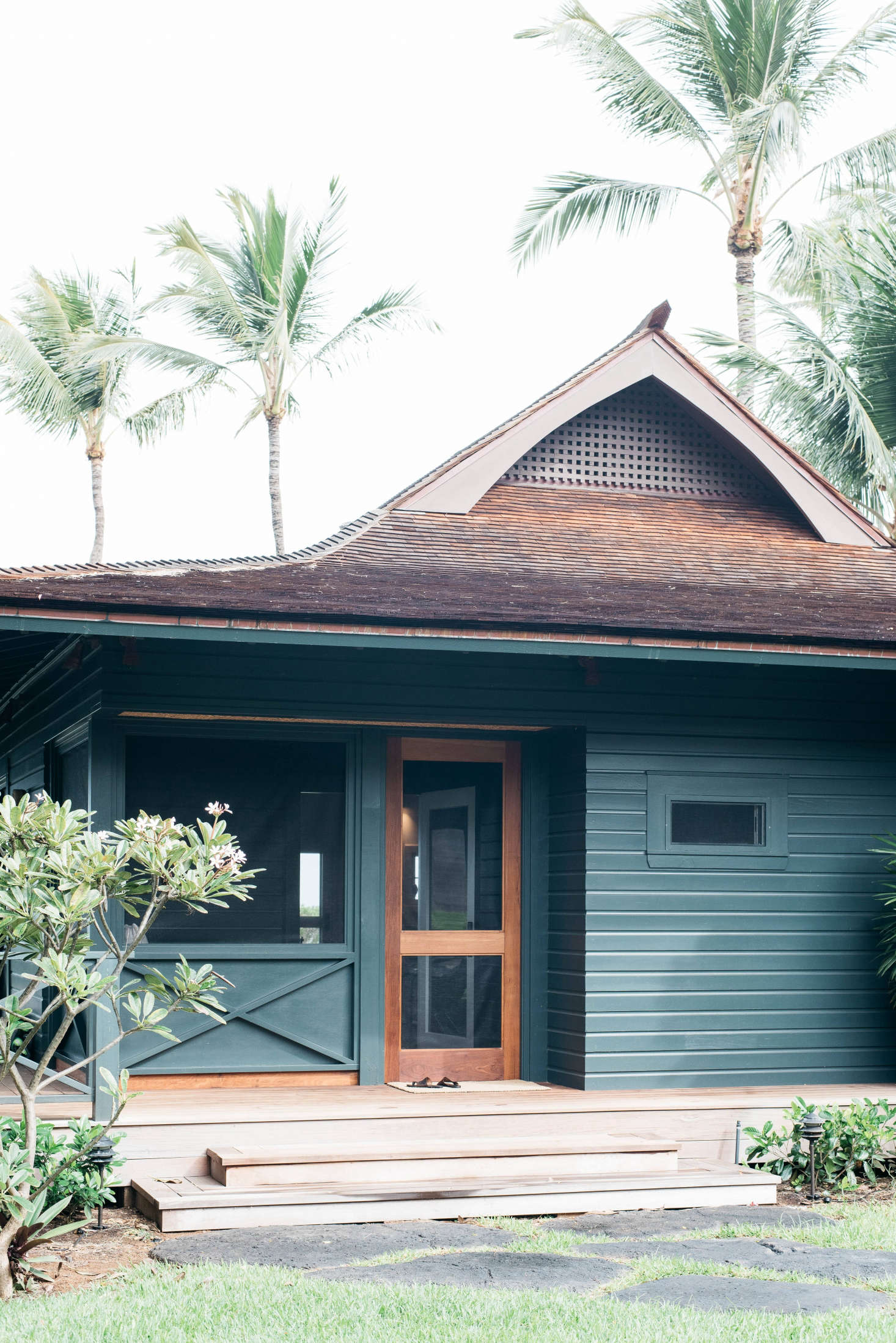 A a traditional plantation cottage, recently restored to its laid-back Hawaiian charm by Brooklyn-based architect Roberto Sosa, has a screened porch with a mahogany door. Photograph by Kate Holstein, from Vacation Rental: Maui Beach Cottage with a Tropical Garden.