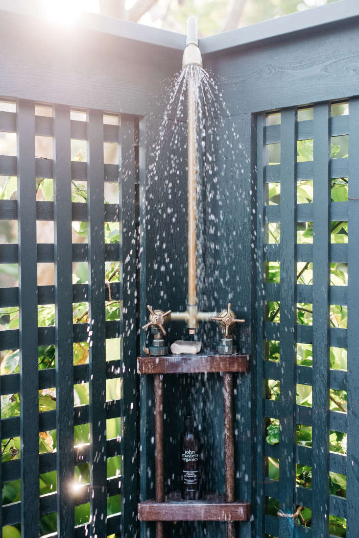 Wooden lattice, painted in the same shade as the house, creates privacy for an outdoor shower but still allows for glimpses of green leaves and vines. The shower fixtures are from Chicago Faucets.