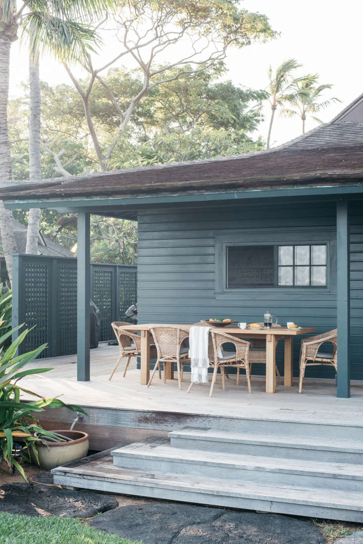 On a low wooden deck outside the kitchen is a dining area for outdoor meals. A discreet spigot and a ceramic planter for hose storage are next to the steps.