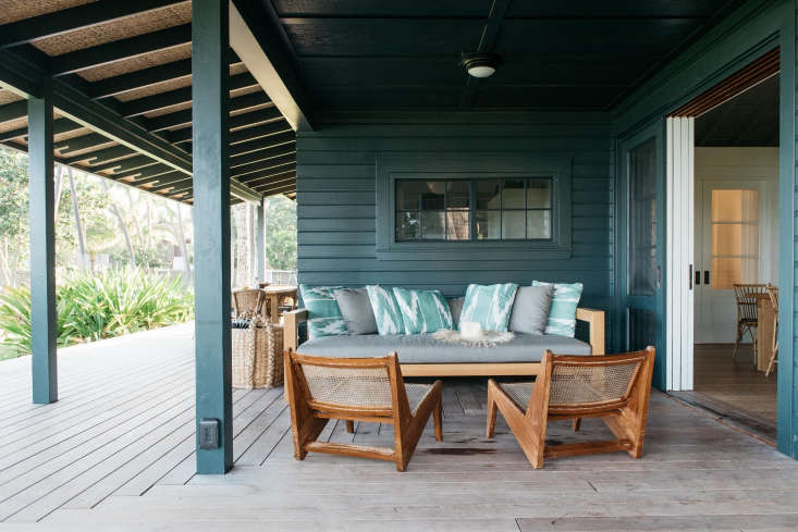 Around the corner on the wide porch of the Beach Cottage is asitting area, anchored by two Pierre Jeanneret caned teak chairs.
