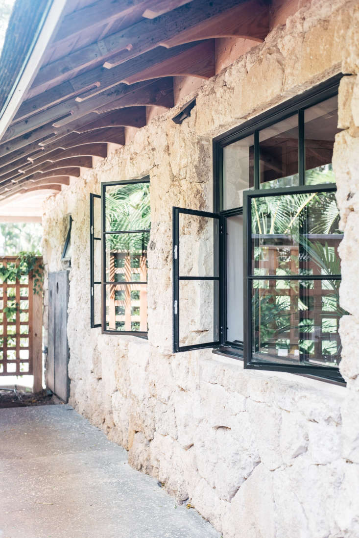 The exterior wood siding of the Carriage House was replaced with coral stone. Forest green aluminum casement windows swing outwards. (For similar styles, see Hardscaping loading=