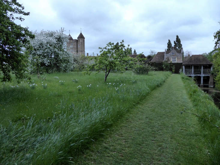 A mown meadow path beside the moat at dawn.