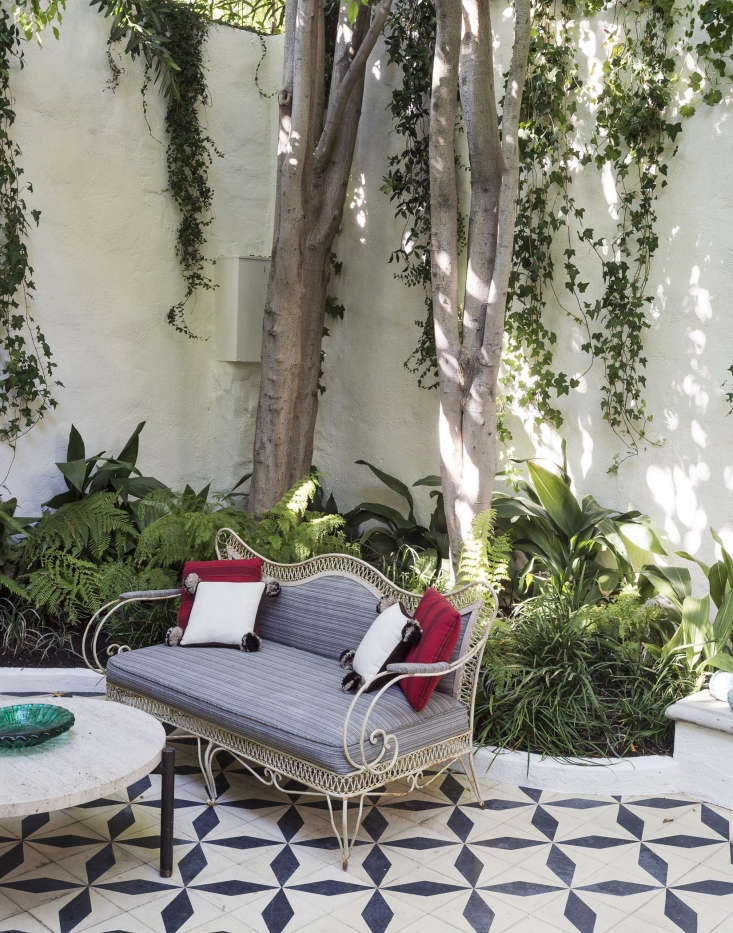 A vintage sofa with cushions upholstered with outdoor fabric will stand up to the elements in a Los Angeles courtyard.