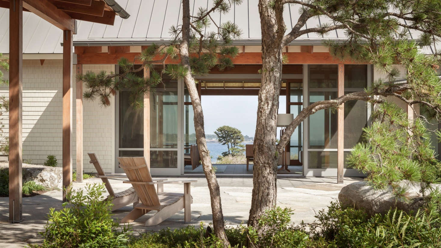 Bordered by full-height sliding glass doors, the living room links a courtyard in front of the house to a patio on the opposing side. The landscape architect planted pitch pine here, centered on the axis of asingle large pitch pine hovering over the water&#8