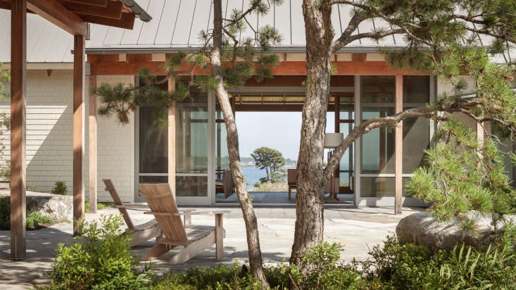 Bordered by full-height sliding glass doors, the living room links a courtyard in front of the house to a patio on the opposing side. The landscape architect planted pitch pine here, centered on the axis of a single large pitch pine hovering over the water&#8