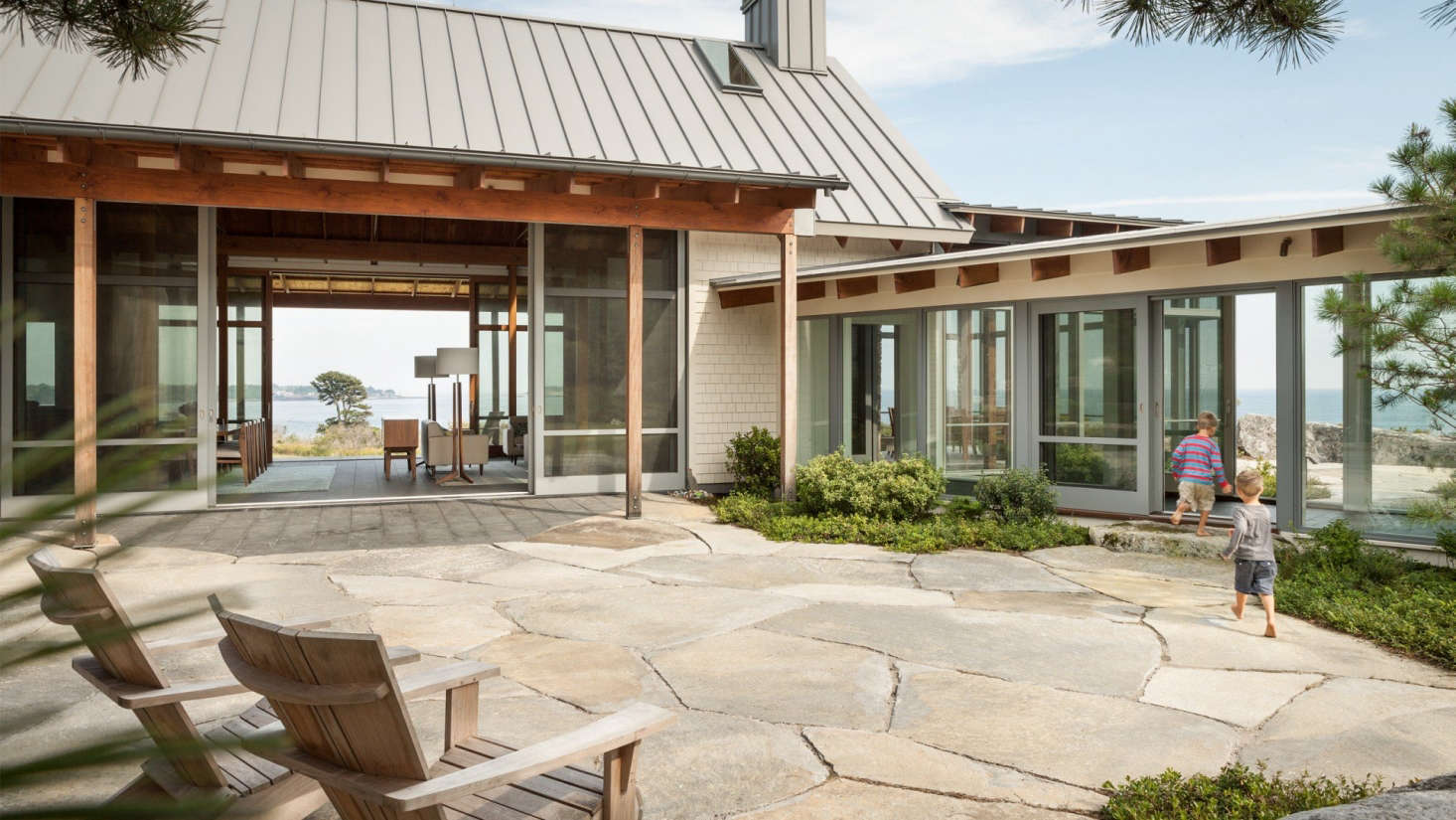 A glass walkway connects the main living volume to the bedroom wing. Sliding glass doors link the courtyard to the fire pit beyond.