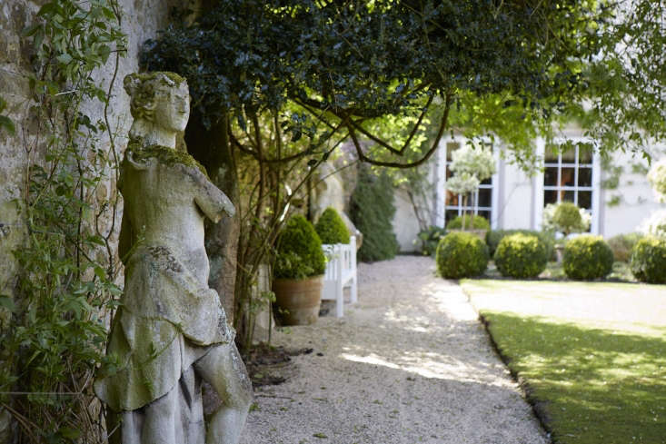 From the original th-century house, terraces lead out to the walled garden, watched over by antique statues and divided by yew buttresses.