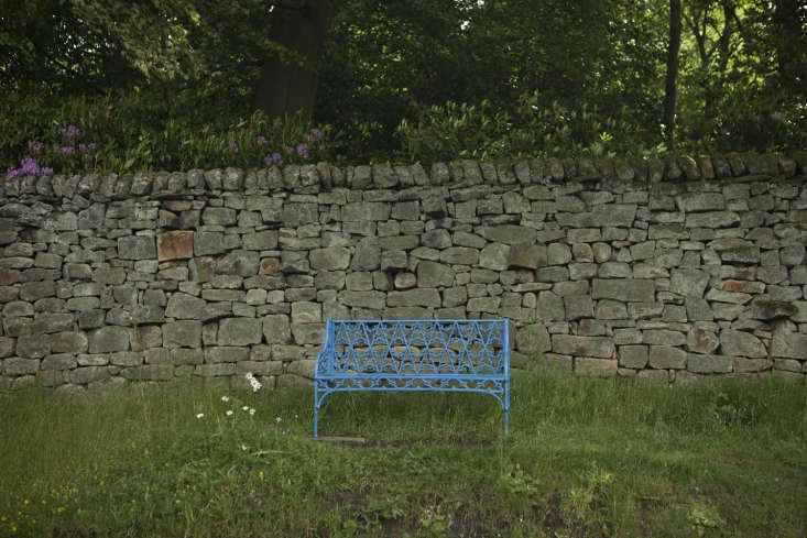 Benches in Chatsworth blue sit along the top of the kitchen garden, which is backed by acres of woodland.