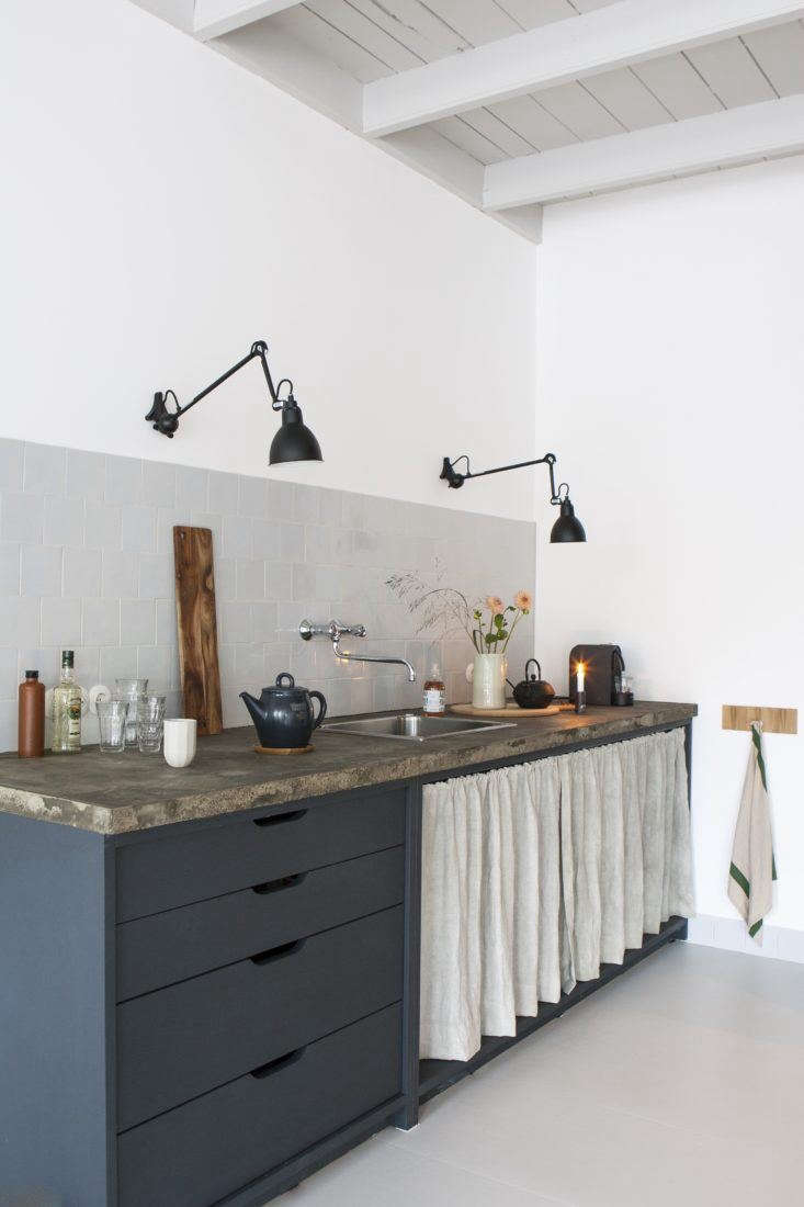 Cutout cabinet pulls and a DIY under-counter curtain confer instant style to a budget kitchen. See more in this week&#8\2\17;s \10 Favorites post.