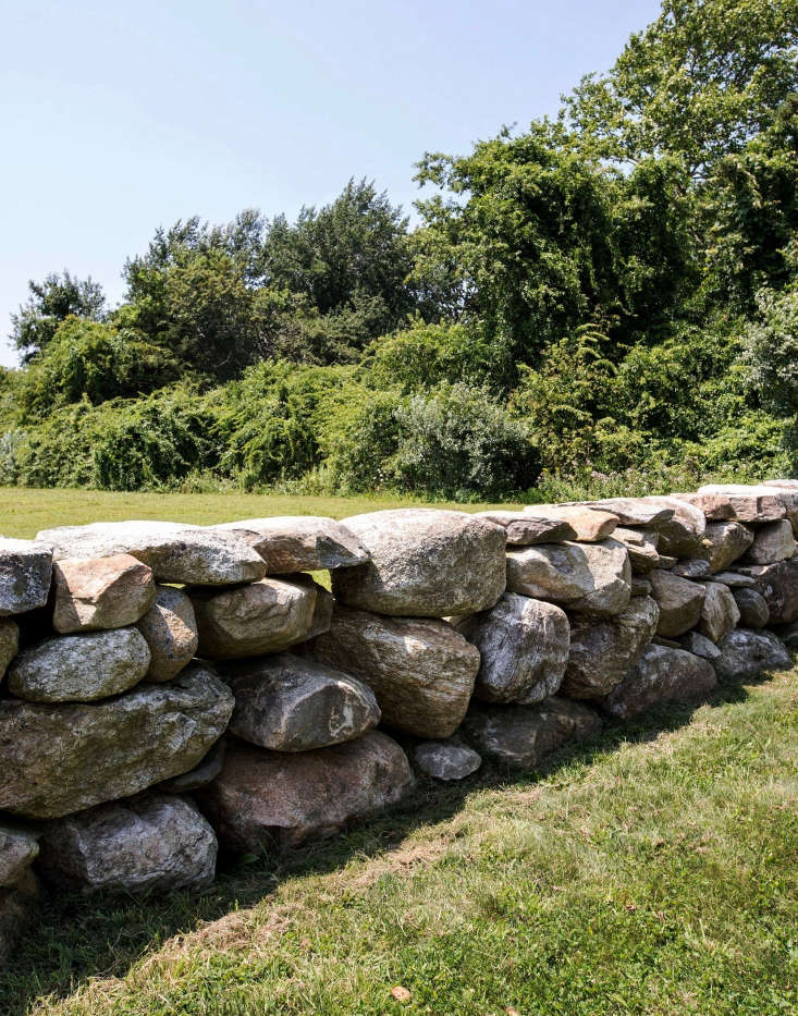 A low, stacked stone wall creates a sense of enclosure around the main house.