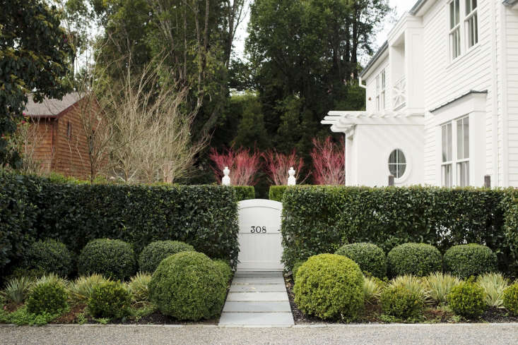 A gracious hedge and charming gate welcome visitors to architect Barbara Chambers&#8