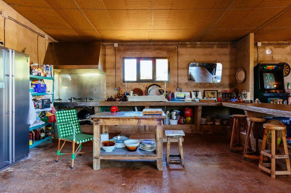 What had been the main sales room is now a cozy kitchen with a potting table as an island. The designers introduced a stainless-steel refrigerator and range, and put the existing wood counter and bins to good use.