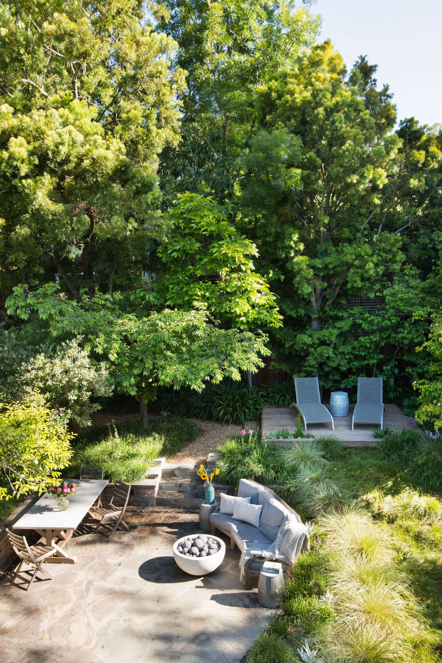 From a bedroom balcony, you look down into a backyard meadow full of flowing grasses. A raised wooden platform with lounge chairs is in the spot once occupied by a  backyard trampoline.