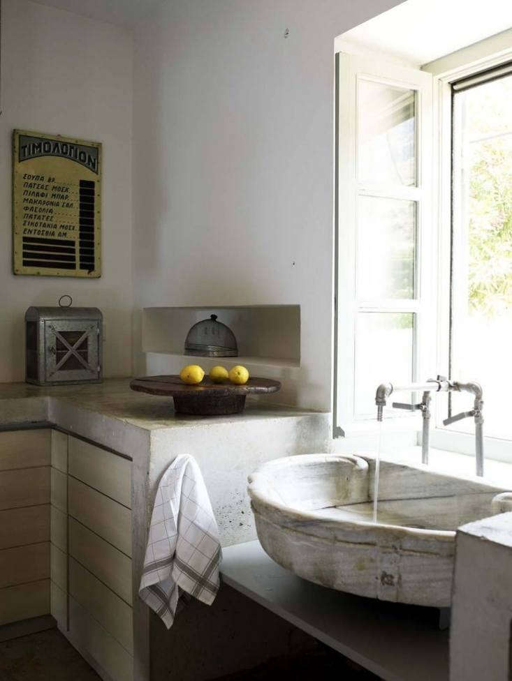 An antique marble fountain basin serves as the sink in our Kitchen of the Weekon the Greek island of Hydra. Photograph by Studio Paterakis, courtesy of Zoumboulakis Architects.