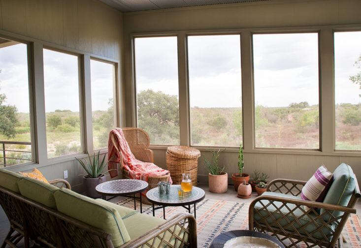 "Austin-based interior designer Ann Edgerton designed a screened porch with a soft bohemian look using vintage rattan furniture, Moroccan accents, and bright textiles. ""I wanted to create a place you can grow into with new textiles and plants,"" she says. Photograph by Molly Winters courtesy of Ann Edgerton, from Steal This Look: A Bohemian Screened Porch in Texas."