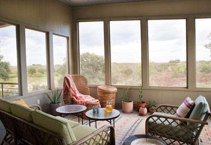 """Austin-based interior designer Ann Edgertondesigned ascreened porch with a soft bohemian look using vintage rattan furniture, Moroccan accents, and bright textiles. """"I wanted to create a place you can grow into with new textiles and plants,"""" she says. Photographby Molly Winters courtesy of Ann Edgerton, from Steal This Look: A Bohemian Screened Porch in Texas."""
