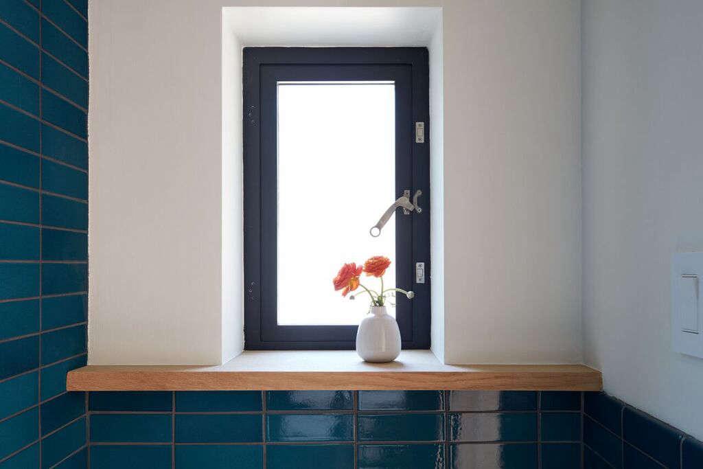 A Heath bud vase holds wildflowers on the bathroom window ledge.