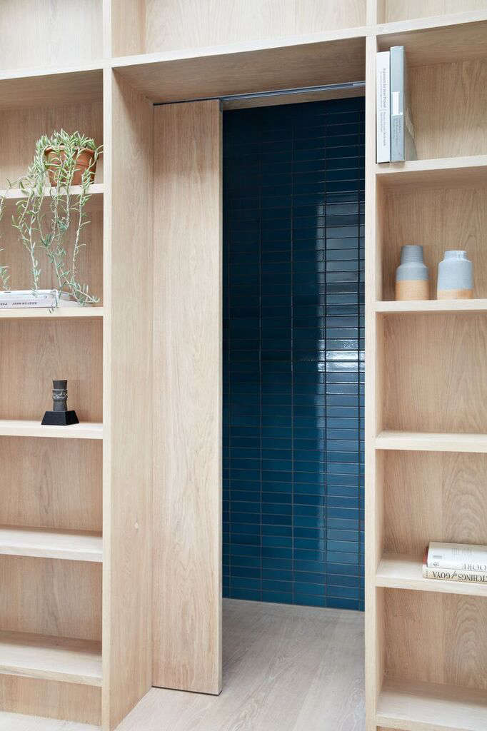 Toward the back of the studio, a white oak pocket door between two bookshelves slides open to reveal the powder room (and a riot of blue).
