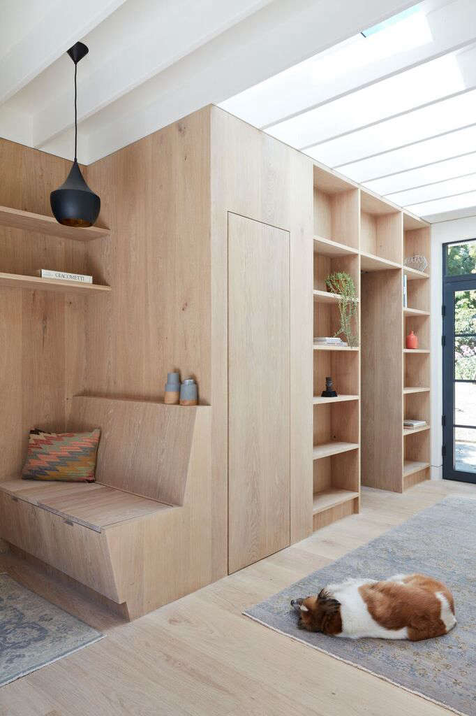 A study in small-space living: Choe packed built-in shelves, a pocket-sized WC, and a concealed utility closet along one wall. It looks streamlined, even spacious, thanks to the uniform white oak.