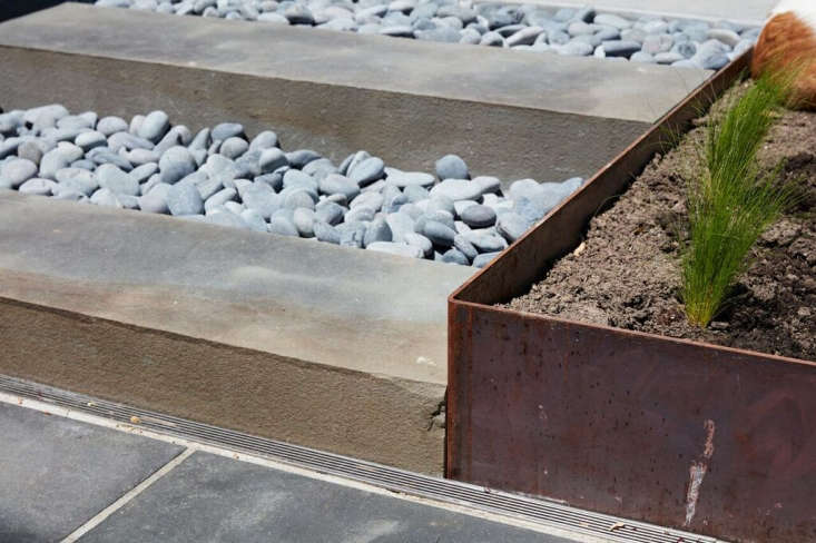 A set of bluestone and river rock steps connects the two levels of the patio. For continuity, Choe used thesame bluestone from the upper patio; the rocks are La Paz beach pebbles. At right: the corner of the Cor-ten steel garden bed. (For more, see Landscaping Ideas: 8 Surprising Ways to Use Cor-ten Steel in a Garden.)