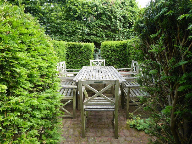 A dining area in the middle of the garden is surrounded by a clipped yew hedge that instantly creates an intimate protected spot. The hedge grows deliberately close to the table and chairs creating a feeling of enclosure.