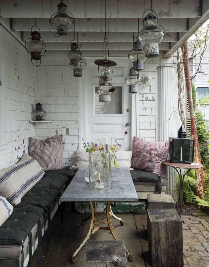 A covered brick patio serves as an outdoor dining area at designer John Derian&#8