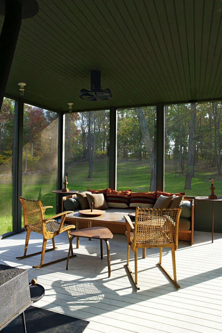 Architects Calvin Tsao and Zack McKown's screened porch at their weekend place in Rhinebeck, New York has  pleasing blend of green walls (so dark they border on Gothic) and midcentury Danish antiques. Photograph by Richard Powers for Tsao & McKown Architects, from Steal This Look: The Perfect Screened Porch.
