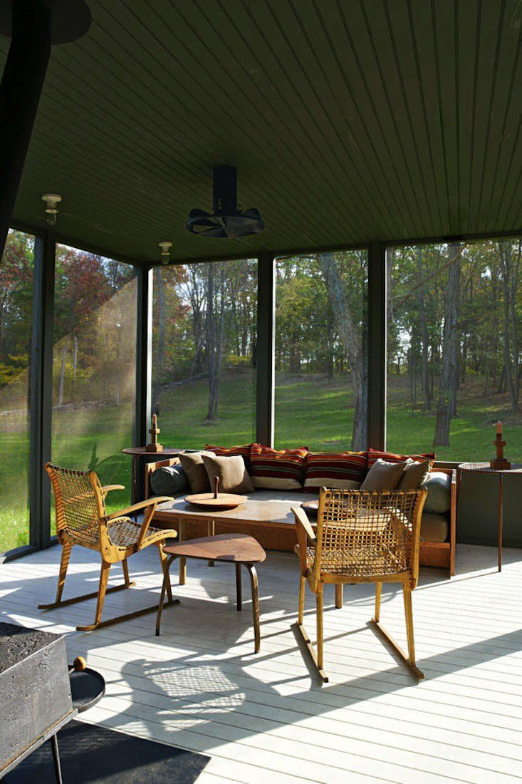 Architects Calvin Tsao and Zack McKown's screened porch at their weekend place in Rhinebeck, New York has pleasing blend of green walls (so dark they border on Gothic) and midcentury Danish antiques.Photograph by Richard Powers for Tsao & McKown Architects, from Steal This Look: The Perfect Screened Porch.