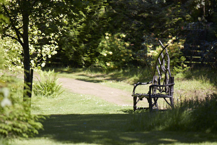 Rustic furniture will blend beautifully with the natural surroundings.Here, a delicate bench crafted from trunks and sticks provides a charming spot to contemplate the garden.