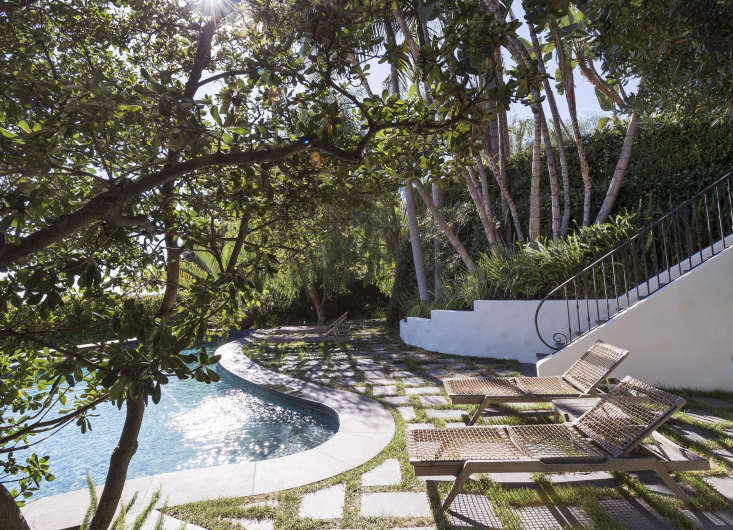 """Edging a swimming pool in Los Angeles, black Cantera stone pavers set in a herringbone pattern are """"grouted"""" with plugs of turfgrass.For more of this project, see our new bookGardenista: The Definitive Guide to Stylist Outdoor Spaces."""