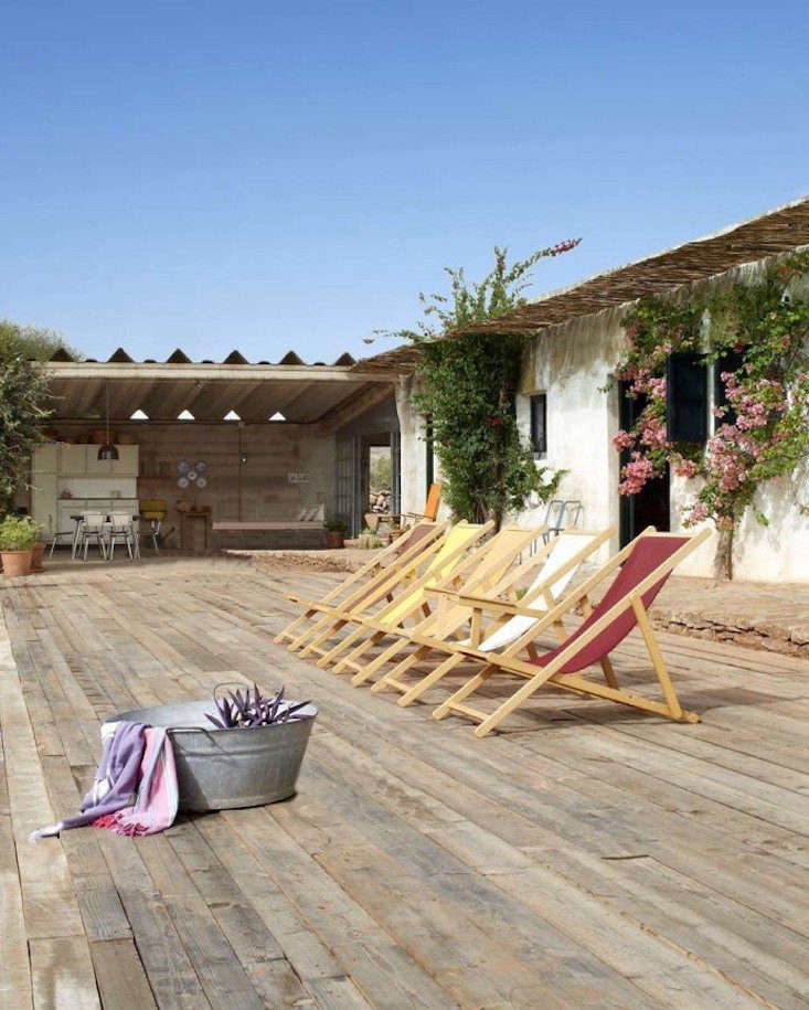 A wicker pergola provides shade and a deck adjoins a large covered patio with a concrete floor.