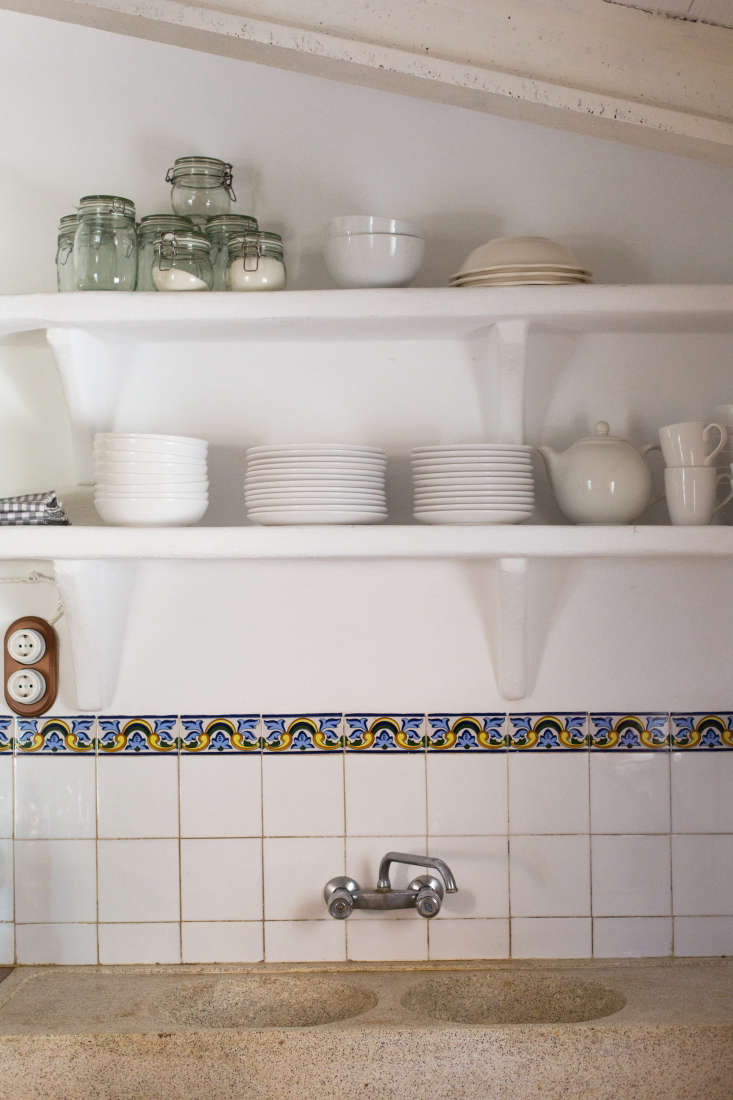 In the kitchen, a double sink and open shelving share a welcoming workspace.