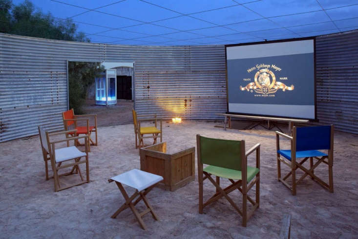 An old water tank is now a sandy-floored outdoor movie theater.